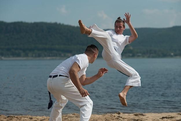 Homens treinam capoeira na praia Foto Premium