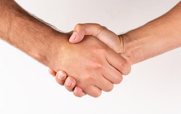 Homens vista lateral, apertar mão, sinal acordo Foto gratuita