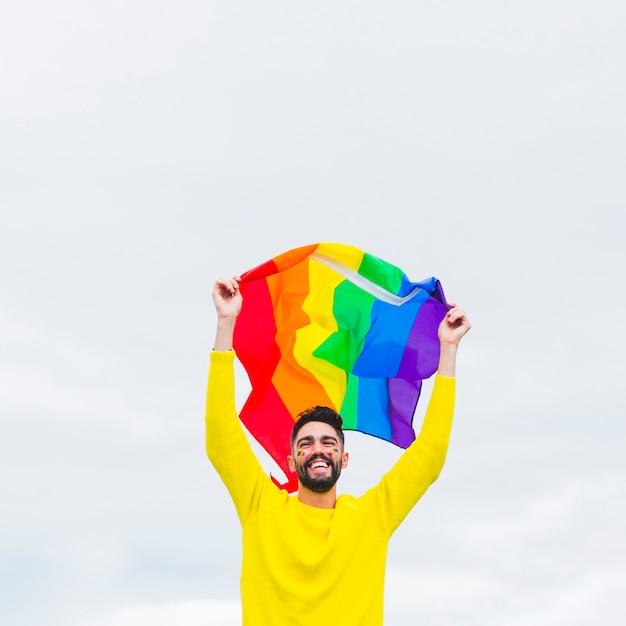 Homossexual em pé e segurando a bandeira lgbt sobre a cabeça Foto gratuita