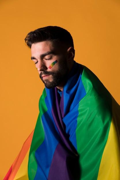 Homossexual, homem, embrulhado, em, lgbt, bandeira arco-íris Foto gratuita
