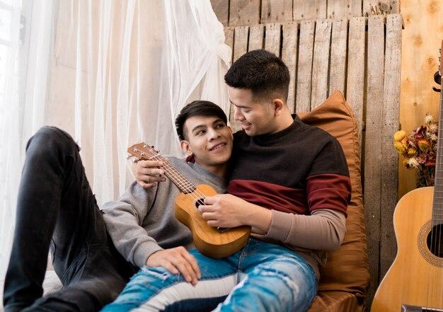 Homossexual masculino de lgbt que tem o divertimento jogar a guitarra junto. Foto Premium