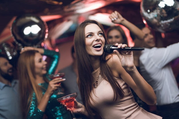 Hora da festa. closeup mulher cantando karaokê Foto Premium