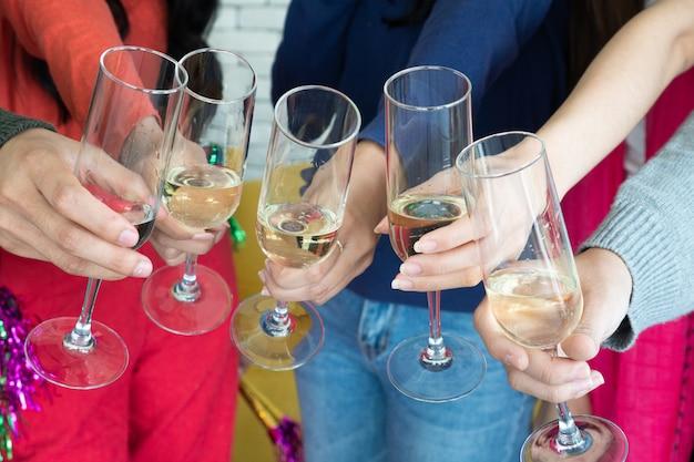 Hora da festa de natal. jovens asiáticos brindando com taças de champagne. amigos, parabenizando-se com o ano novo. Foto Premium