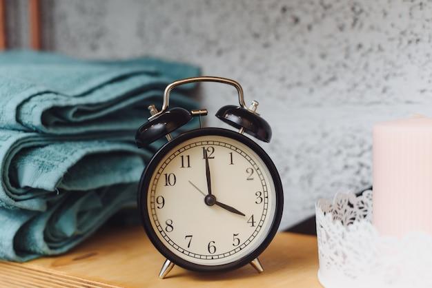 Hora da massagem relógio preto analógico em uma prateleira com toalhas azuis e velas de cera. o conceito de itens de massagem Foto Premium