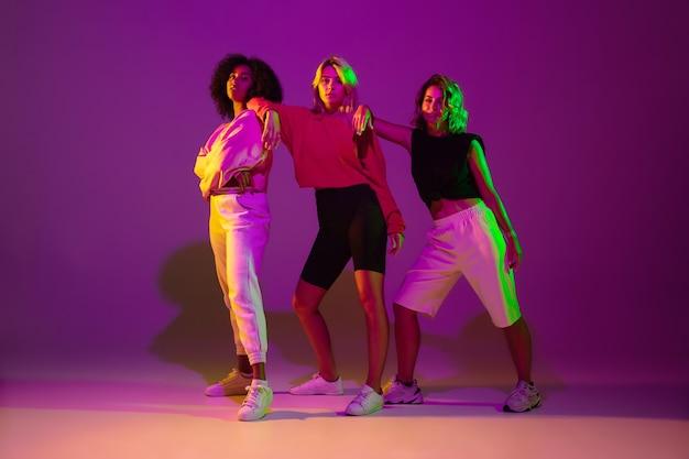 Hora de dançar. homens elegantes e mulher dançando hip-hop em roupas brilhantes sobre fundo verde no salão de dança em luz de néon. Foto gratuita