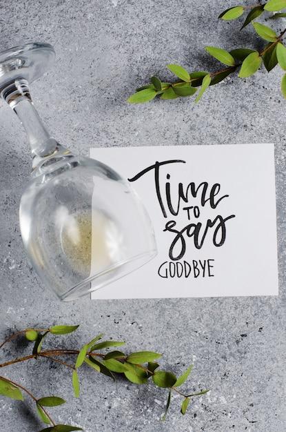 Hora de dizer adeus. a inscrição em uma folha de papel branco. vinho branco em um copo de vidro. Foto Premium