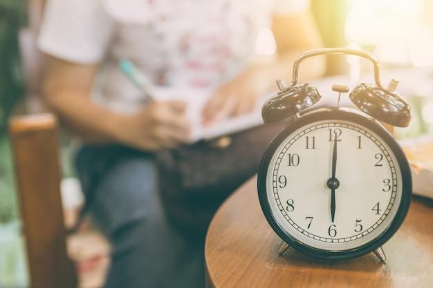 Hora de trabalhar o conceito. relógio cronometrado às 8 horas com borrão pessoas que trabalham fundo. Foto Premium