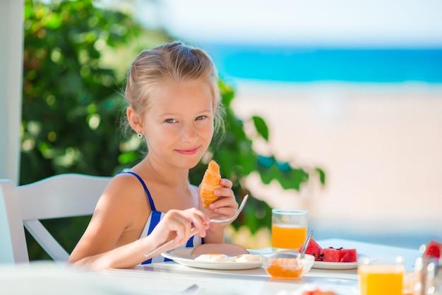 Hora do almoço. menina tomando café da manhã no café ao ar livre com vista para o mar Foto Premium