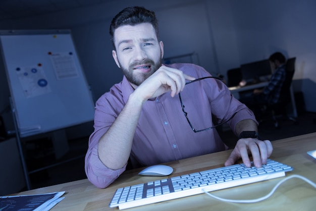 Hora extra. homem de ti cansado e bonito tirando os óculos e descansando do trabalho enquanto está sentado em frente ao computador Foto Premium