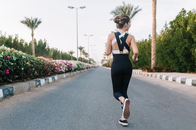 Horário de verão da jovem alegre volta a correr na rua com palmeiras, flores coloridas na cidade tropical. humor alegre, se divertindo, treino, manhã ensolarada, modelo atraente. Foto gratuita