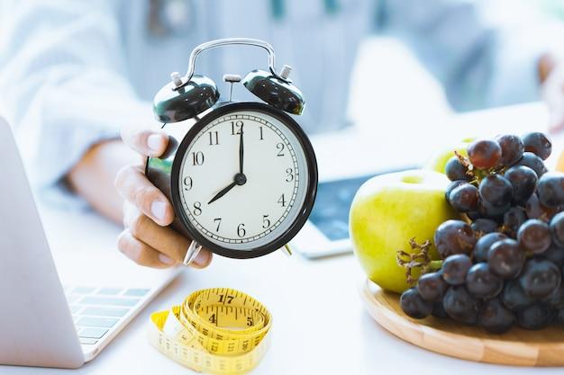 Horário para cuidados com a saúde ou dieta conselheiro de alimentos mostre o relógio para cronometrar cuide de sua saúde com comida saudável e conceito. Foto Premium