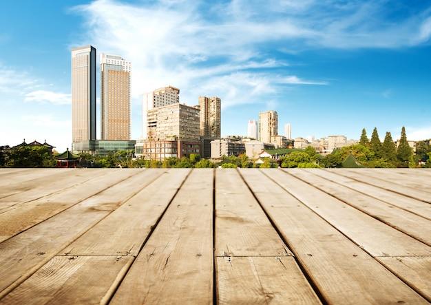 Horizonte panorâmico e edifícios com tabuleiro de madeira vazio Foto Premium