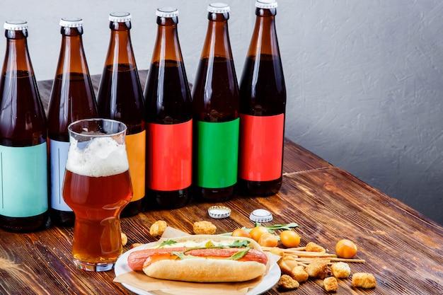 Hotdog e cerveja em uma placa de madeira. Foto Premium