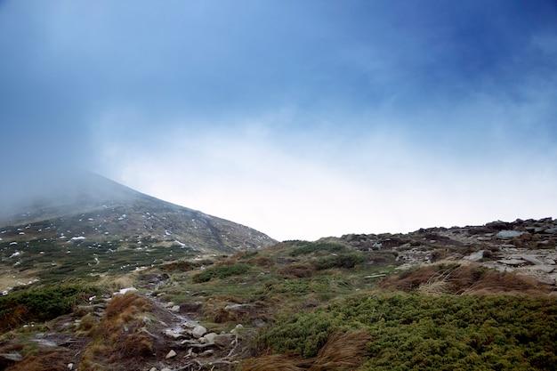 Hoverla, topo de uma montanha parcialmente coberta de neve e nevoeiro matinal. Foto Premium