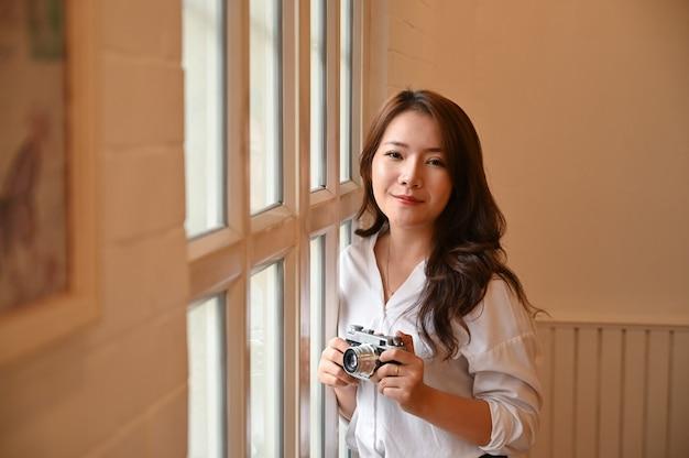 Hs da fêmea segurando a câmera vintage retrô. Foto Premium