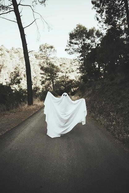 Humano em traje fantasma levantando as mãos na rota rural Foto gratuita