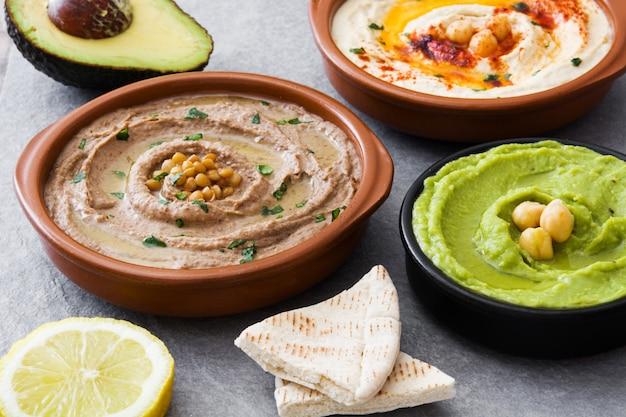 Hummus de grão de bico, hummus de abacate e hummus de lentilhas na pedra cinza Foto Premium