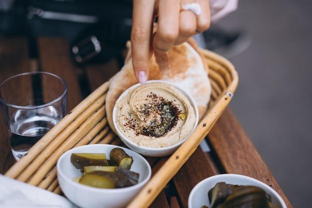 Hummus delicioso fresco, pão pita e pepinos em conserva Foto gratuita