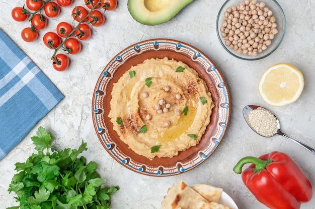 Hummus em uma placa de argila marrom com um padrão azul. na mesa branca são vegetais, verduras, pedaços triangulares de pita. vista do topo. lay plana. Foto Premium