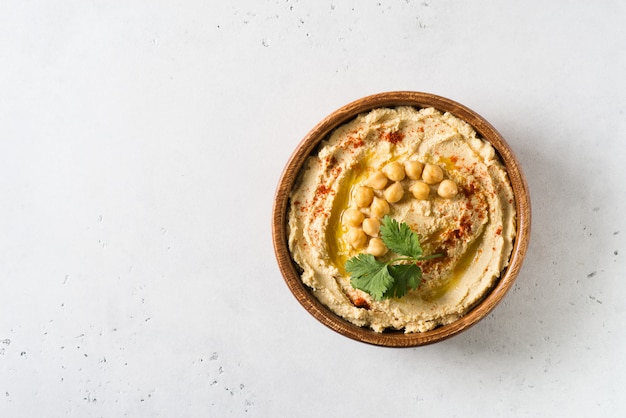 Hummus mergulho com grão de bico e salsa em placa de madeira no fundo branco Foto Premium