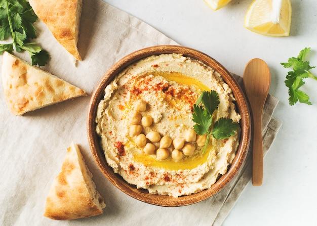 Hummus mergulho com grão de bico, pita e salsa em placa de madeira no fundo branco Foto Premium