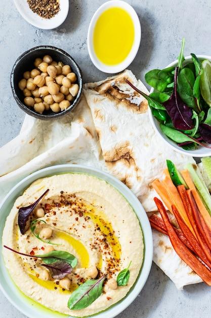 Humus clássico em uma tigela com ervas, páprica defumada, azeite e alface em um fundo azul (cinza). comida vegetariana saudável. Foto Premium