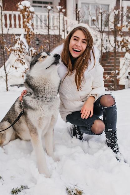 Husky engraçado descansando após o jogo no parque nevado. retrato ao ar livre da elegante mulher branca em jeans rasgados, sentado no chão perto de seu lindo cachorro no fim de semana de inverno. Foto gratuita