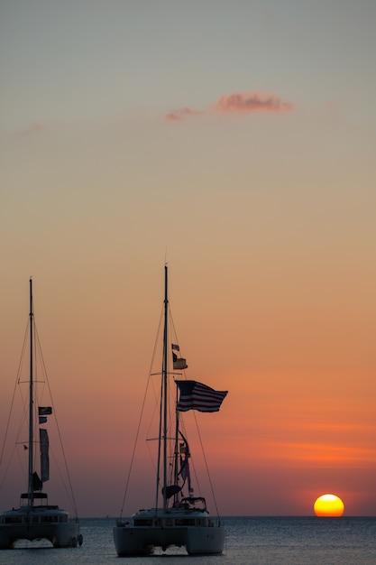 Iate no mar durante o pôr do sol Foto gratuita