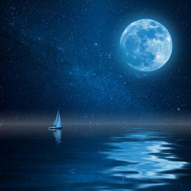 Iate solitário no oceano calmo, lua cheia e estrelas reflexo na água Foto Premium