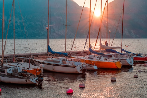 Iates no cais durante o pôr do sol no lago de garda. pôr do sol na riva del garda. o sol se põe nas montanhas. lago no norte da itália. Foto Premium