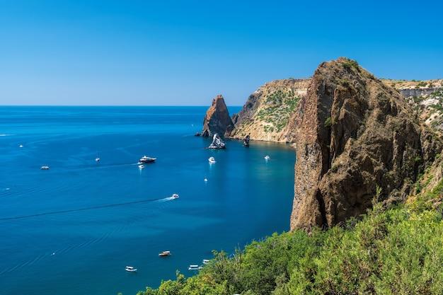 Iates no mar em um fundo de costões rochosos. paisagem do mar com iates e litoral rochoso. copie o espaço. o conceito de uma viagem, relaxamento, vida ativa e saudável em harmonia com a natureza. Foto Premium