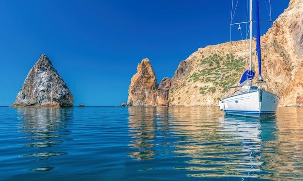 Iates no mar em um fundo de costões rochosos. paisagem do mar com iates e litoral rochoso. copie o espaço. Foto Premium