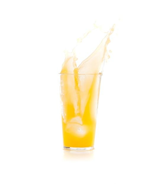 Ice caindo em um copo com bebida amarela Foto gratuita