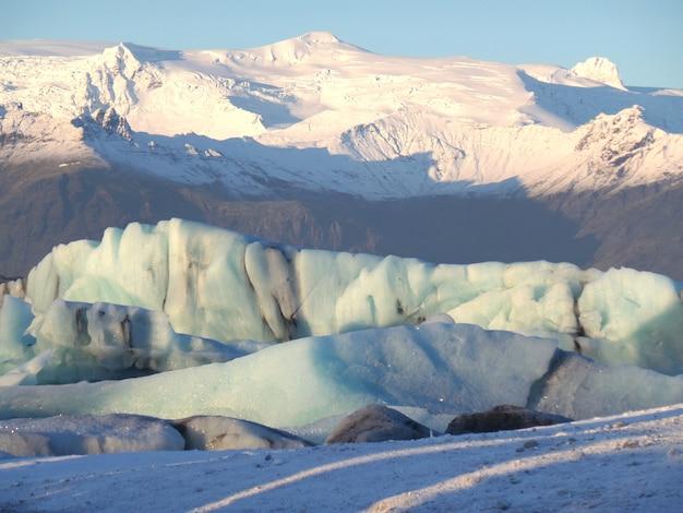 Icebergs enormes flutuando contra a montanha coberta de neve Foto Premium