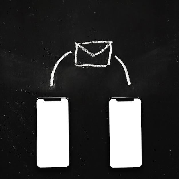 Ícone de mensagem desenhada sobre o celular em branco dois na lousa Foto gratuita