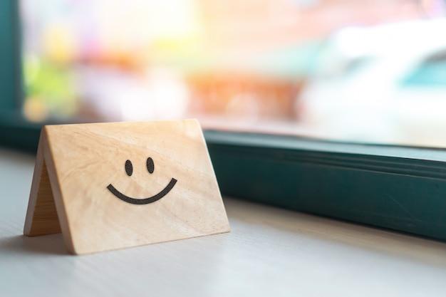 Ícone de rosto sorriso na placa de sinal de madeira. pessoa otimista ou pessoas que se sentem dentro e classificação de serviço, conceito de satisfação. Foto Premium