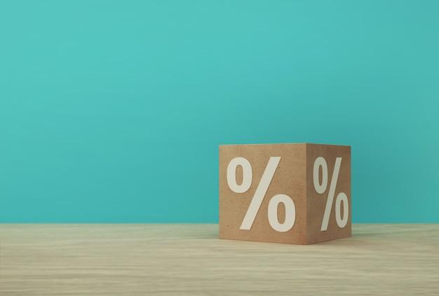 Ícone de símbolo de sinal de porcentagem com bloco de cubo de papel na mesa de madeira e fundo azul. Foto Premium