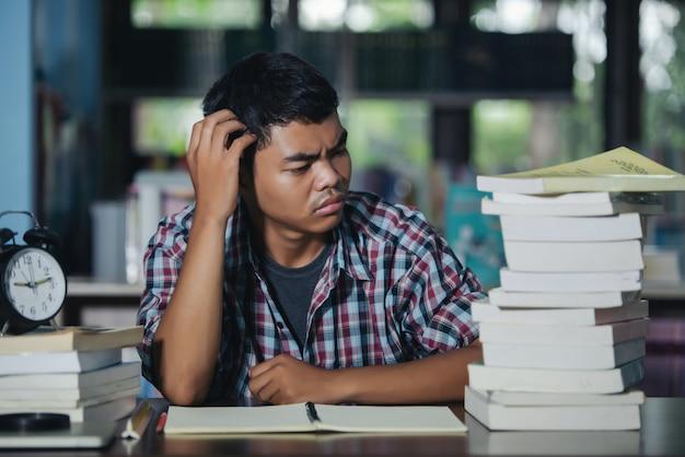 Ícone educacional: aluno cansado em uma biblioteca Foto gratuita