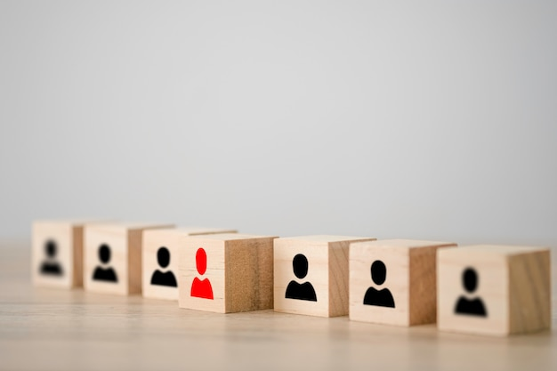 Ícone humano vermelho em um cubo de madeira na frente de outros cubos de madeira do ícone humano preto. liderança e conceito de pensamento diferente. Foto Premium