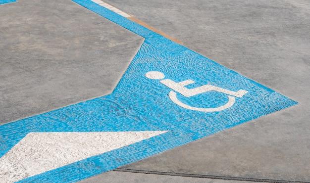 Ícone para deficientes no chão da reserva de área de estacionamento para pessoas com deficiência no posto de gasolina urbano Foto Premium