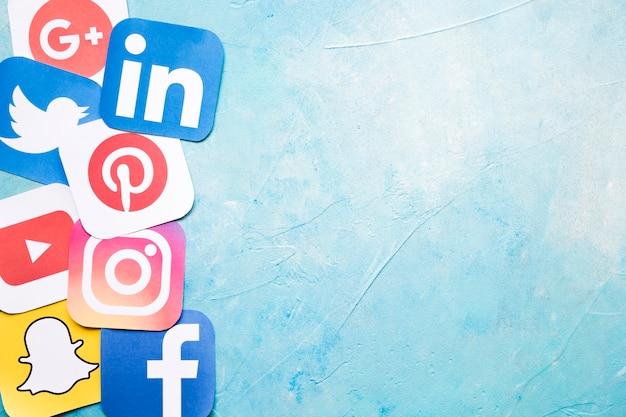 Ícones de diferentes mídias sociais na parede pintada de azul Foto gratuita