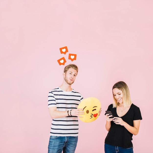 Ícones de forma de coração sobre homem segurando beijo emoji perto de mulher feliz usando telefone celular Foto gratuita