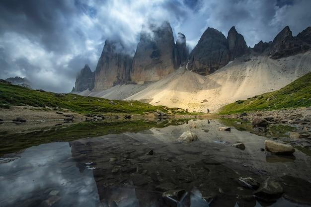 Ideia bonita das paisagens da reflexão da montanha no rio com o céu azul no verão de tre cime, dolomites, itália. Foto Premium
