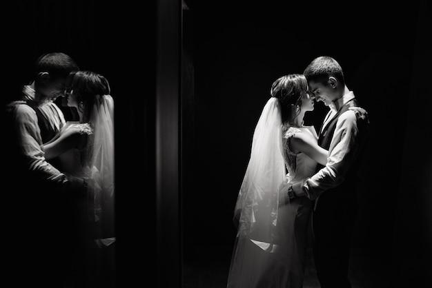 Idéia criativa foto de fotografia de casamento em reflexão. noiva e noivo iluminado por luzes. Foto Premium