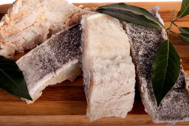 Ideia de um grupo do bacalhau salgado cortado isolado em um fundo branco. Foto Premium