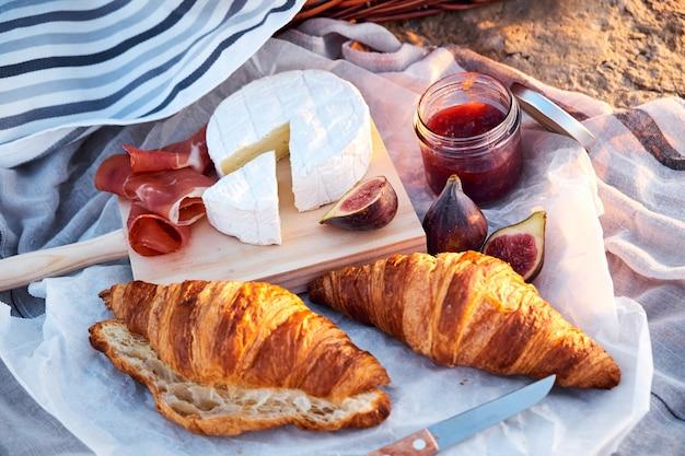 Ideia superior da composição romântica bonita do piquenique com croissants, pão, doce, queijo, figos e jamon. Foto Premium