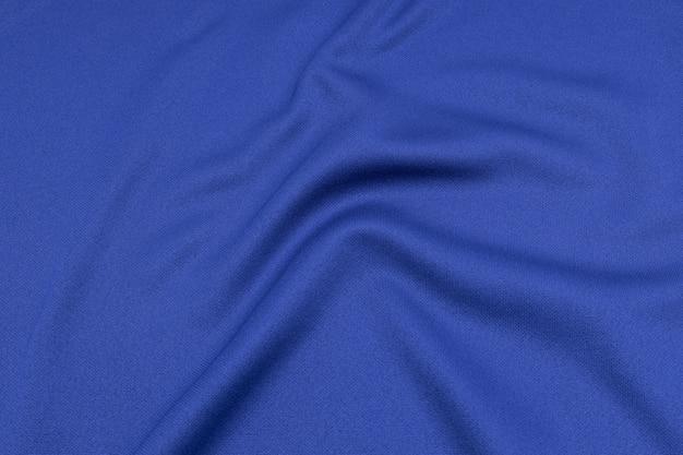 Ideia superior da textura da tela da roupa de esporte da superfície de matéria têxtil de pano. camisa azul do futebol com copyspace. Foto Premium