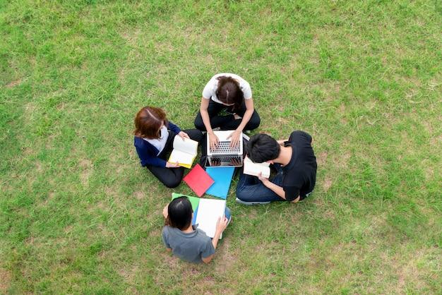 Ideia superior do grupo de estudantes asiáticos que sentam-se junto no parque. Foto Premium