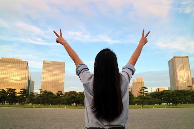 Ideia traseira das mãos asiáticas do aumento da mulher com o céu azul claro, as nuvens brancas e o edifício. Foto Premium
