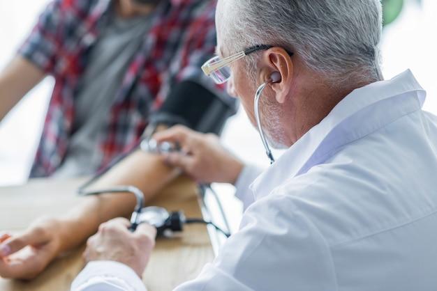 Idoso, doutor, medindo, pressão sangue, de, paciente Foto gratuita